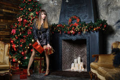 Girl with Christmas gifts. Beautiful girl with Christmas gifts decorated with Christmas tree and fireplace, concept Christmas gifts Stock Images