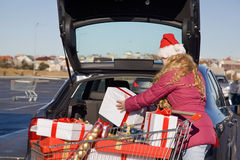 Girl with Christmas gifts near a car. Girl puts Christmas gifts in car trunk parked near shop Stock Images