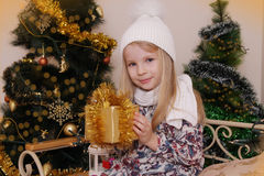 Girl with Christmas golden gift Stock Images