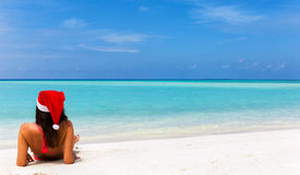 Girl with Christmas hat and bikini lying on tropical beach. At the Maldives Royalty Free Stock Photography