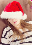 Girl in Christmas hat . the brown chair Royalty Free Stock Photography