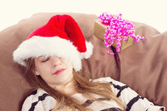 Girl in Christmas hat . the brown chair Royalty Free Stock Photo