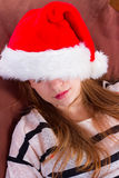 Girl in Christmas hat . the brown chair Stock Photos