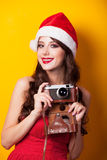 Girl in christmas hat with camera Stock Photos