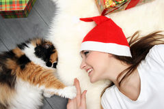 Girl in Christmas hat with cat Stock Photo