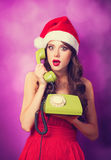 Girl in christmas hat with green telephone Stock Images