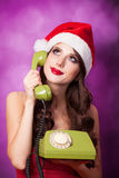Girl in christmas hat with green telephone Stock Photography