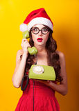 Girl in christmas hat with green telephone Royalty Free Stock Images
