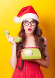 Girl in christmas hat with green telephone Royalty Free Stock Photography