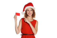 Girl in a Christmas hat holding card Royalty Free Stock Photo
