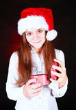 Girl in christmas hat holding gift over dark. Background Royalty Free Stock Photo