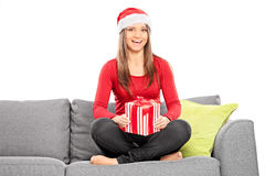 Girl with Christmas hat holding a present. Girl with Christmas hat holding present seated on a sofa isolated on white background Royalty Free Stock Photo