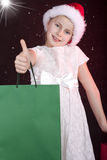 Girl in christmas hat holding shopping bags. Smiling girl in christmas hat holding shopping bags Royalty Free Stock Photo