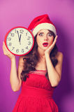 Girl in christmas hat with huge clock Royalty Free Stock Image