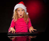 Girl in christmas hat with keybard Stock Images