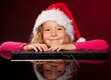 Girl in christmas hat with keybard Royalty Free Stock Photos