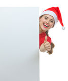 Girl  in Christmas hat looking out from billboard Royalty Free Stock Photo