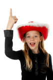Girl with christmas hat is pointing Stock Photo