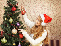 A girl in a Christmas hat posing near the tree Stock Photos