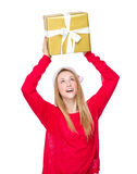 Girl with Christmas hat and raise up the big gift box. Isolated over white background Stock Photo