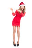 Girl in a Christmas hat and red dress pointing toward.  Royalty Free Stock Images