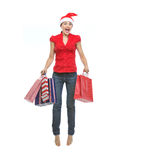 Girl in Christmas hat with shopping bags jumping Stock Photo