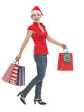 Girl in Christmas hat with shopping bags walking Royalty Free Stock Image