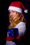 Girl in christmas hat with small present Stock Photos