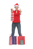 Girl in Christmas hat standing among shopping bags Stock Photography