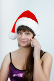 Girl in a Christmas hat talking on a cell phone. Attractive girl in a Christmas hat talking on a cell phone Royalty Free Stock Image