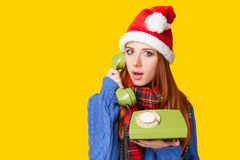 Girl in christmas hat with telephone Royalty Free Stock Photos