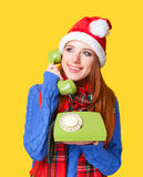 Girl in christmas hat with telephone Royalty Free Stock Photography