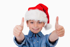 Girl with a Christmas hat and the thumbs up Stock Photography