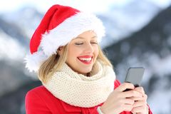 Girl on christmas holidays using smart phone. Happy girl on christmas holidays using smart phone with a snowy mountain in the background Stock Photography