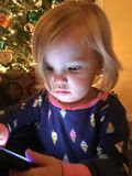 Girl at Christmas. Little girl with light on her face at Christmas time royalty free stock photography
