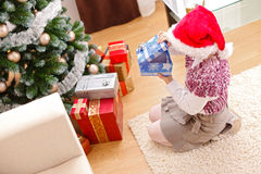 Girl in christmas, looking inside gift box Stock Photos