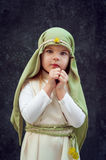 Girl in a Christmas outfit. Attire for the reconstruction of the history of the birth of Jesus Christ. Girl in biblical costume,. Hands folded in prayer royalty free stock photography