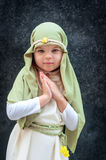 Girl in a Christmas outfit. Attire for the reconstruction of the history of the birth of Jesus Christ. Girl in biblical costume,. Hands folded in prayer royalty free stock photos