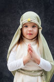 Girl in a Christmas outfit. Attire for the reconstruction of the history of the birth of Jesus Christ. Girl in biblical costume,. Hands folded in prayer royalty free stock images