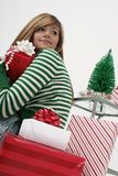 Girl with Christmas presents. A view of a young teenage girl wearing a green striped top with several wrapped Christmas presents or gifts around her and a small Stock Image