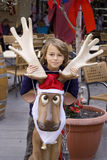 Girl and Christmas reindeer. A girl sitting on a funny statue of a reindeer wearing a christmas hat Stock Photos