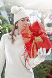 Girl in a Christmas shop with red gift box Stock Images