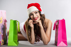Girl with Christmas shopping in the hat of Santa Claus Stock Photography