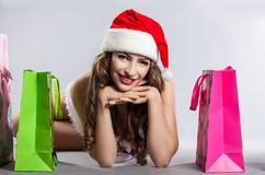 Girl with Christmas shopping in the hat of Santa Claus Stock Photo