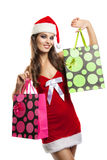 Girl with Christmas shopping in the hat of Santa Claus Stock Images