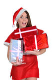 The girl in a Christmas suit rejoices to gifts Stock Photography