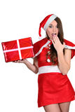 The girl in a Christmas suit is surprised to a gift Royalty Free Stock Photo