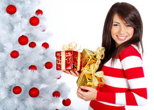 Girl with christmas surprise. Smiling girl with christmas surprise next to white tree Royalty Free Stock Photos