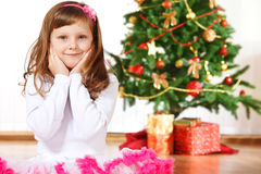 Girl beside Christmas tree Stock Images