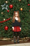 Girl by the Christmas tree Stock Images